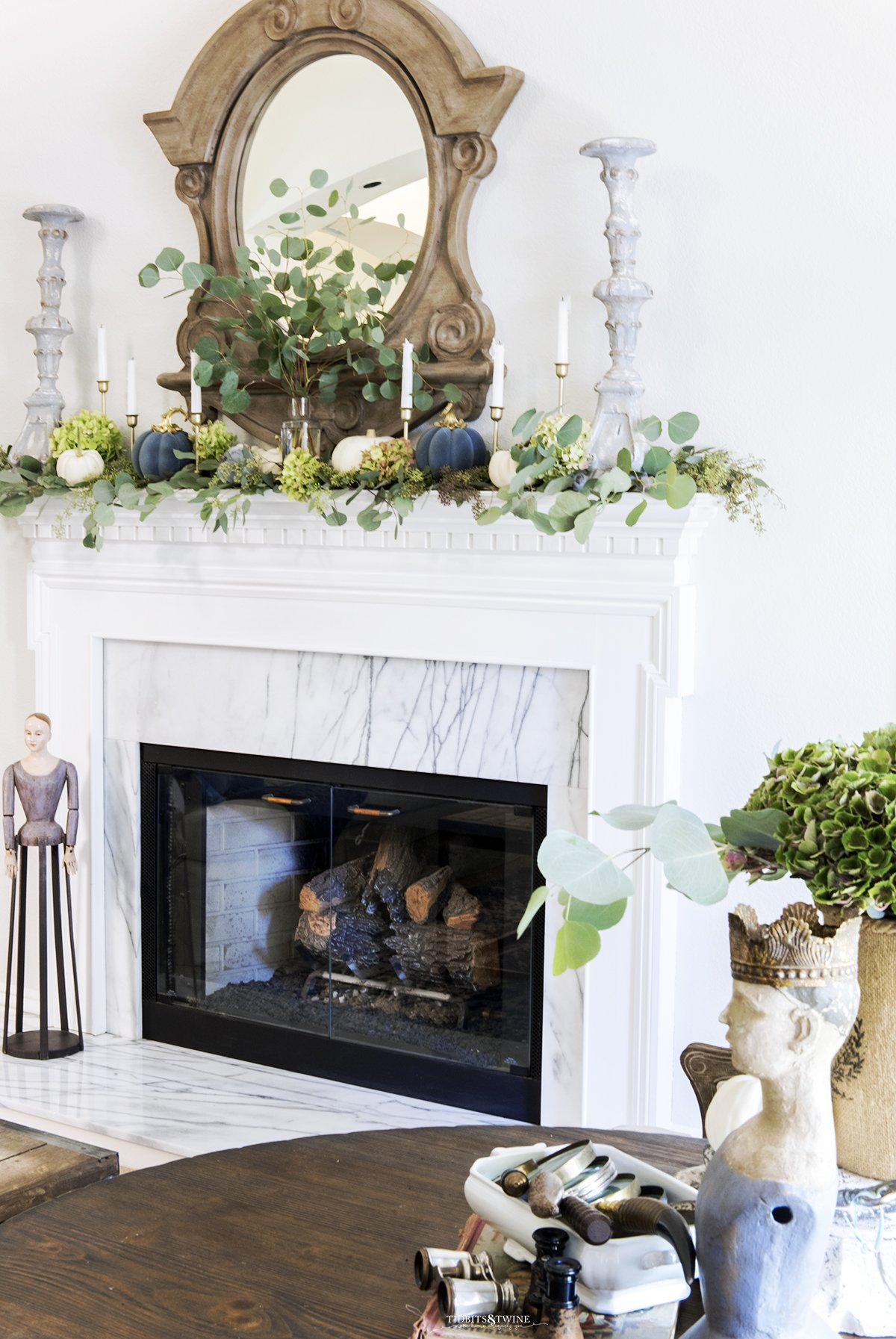White fireplace mantel with French mirror above and eucalyptus and white pumpkins on top