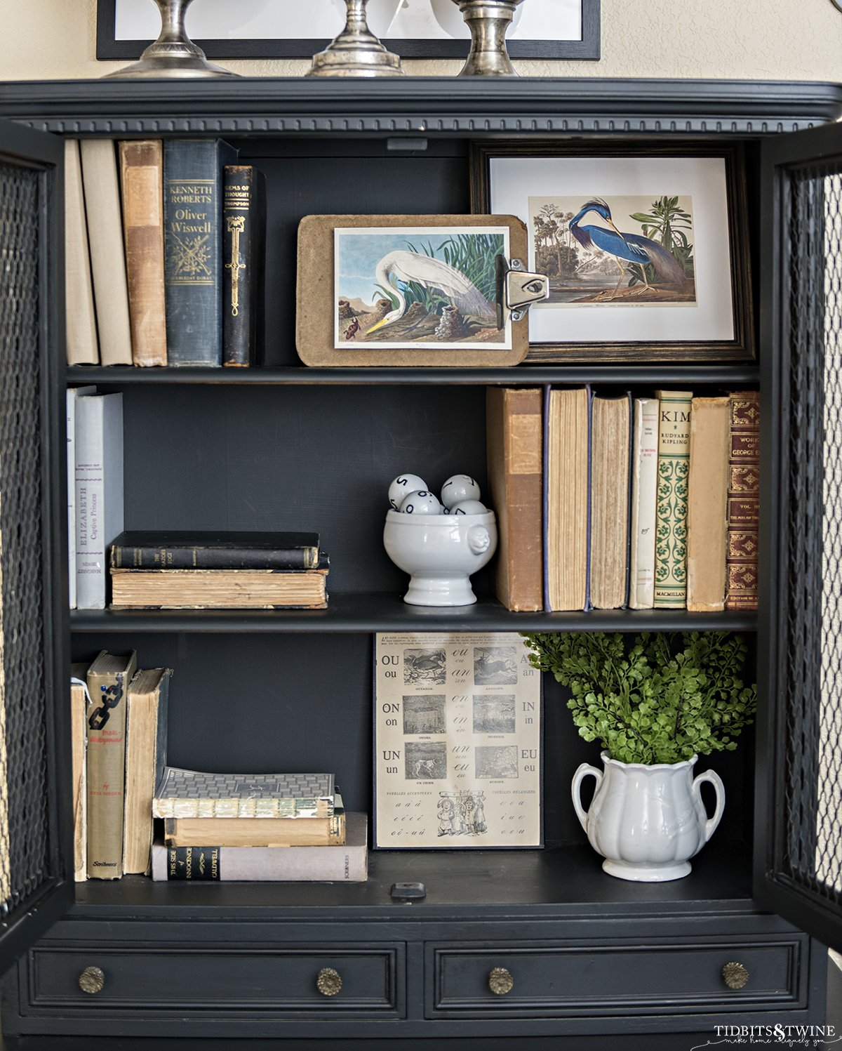Black cabinet with styled shelves holding ntique books and framed bird artwork