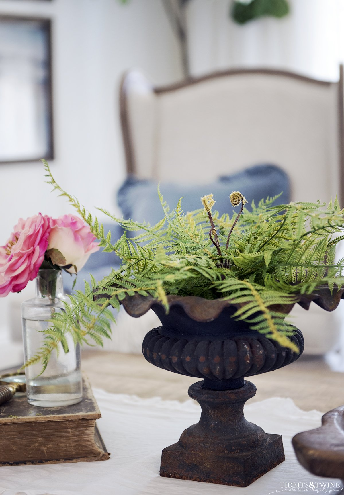 Iron urn with fake fern on coffee table with white runner and old book with pink rose
