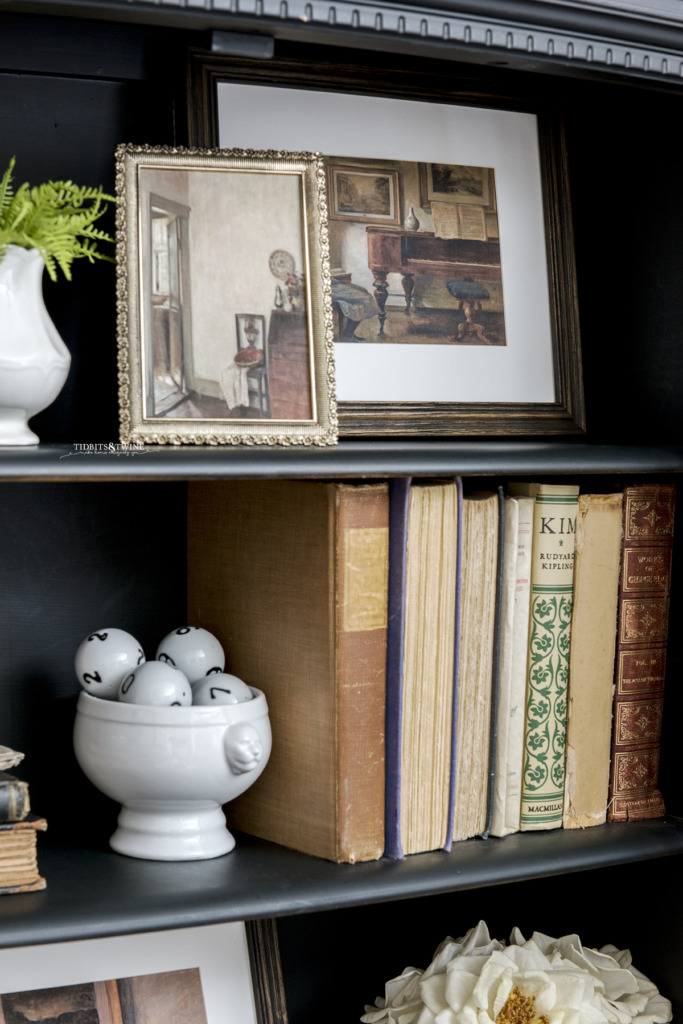 Closeup of black cabinet containing framed downloadable Carl Holsoe artwork and antique books