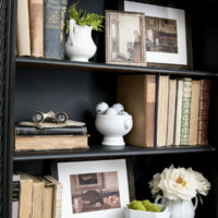Black cabinet with shelves decorated with antique books framed artwork ironstone moss and fake white roses