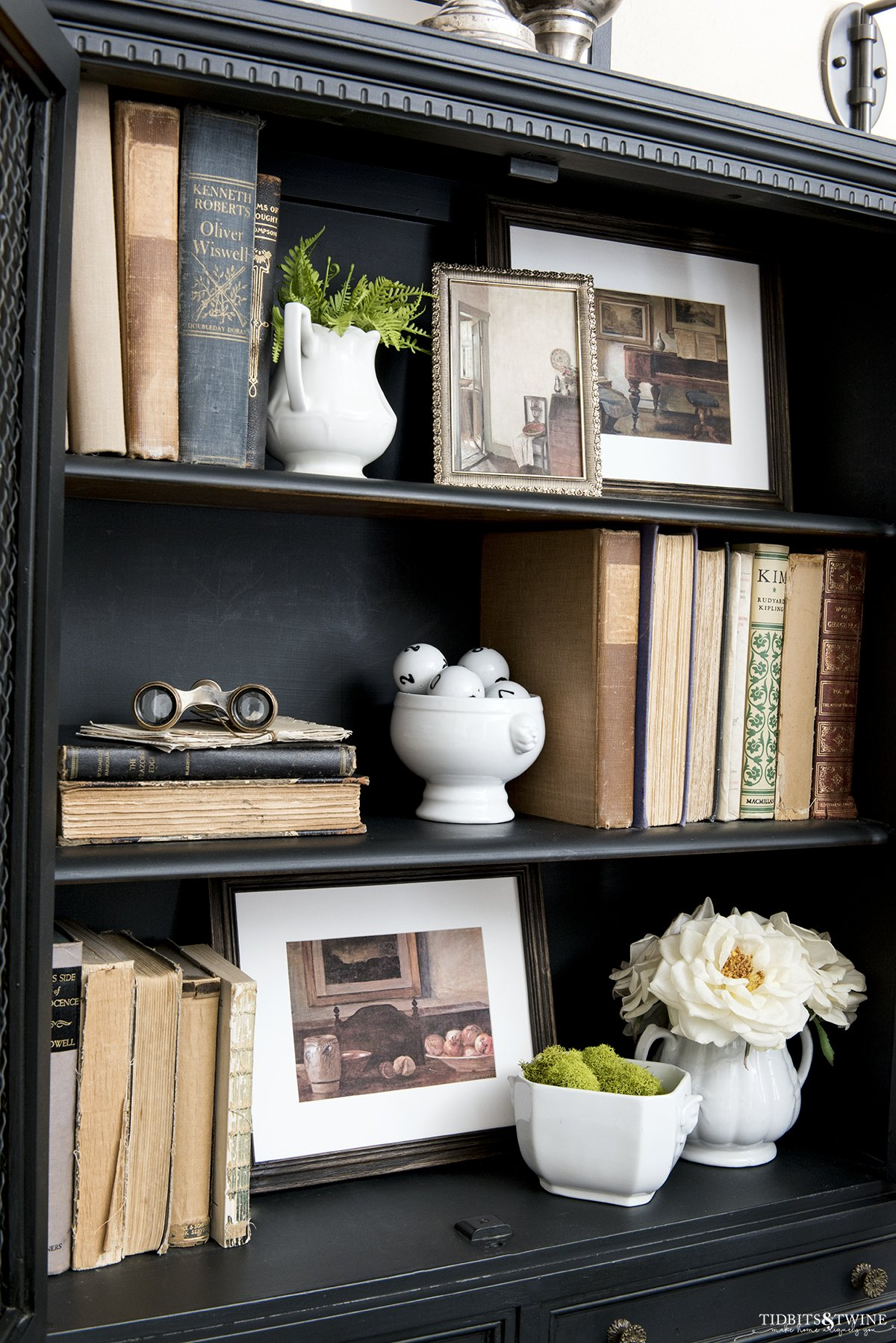 Black bookshelf styled with antique books and framed artwork and a vase of white roses