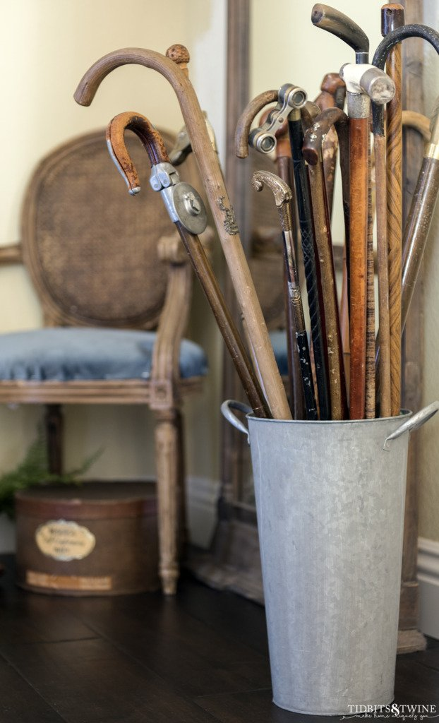 Antique cane collection in metal bucket in entryway with chair in background