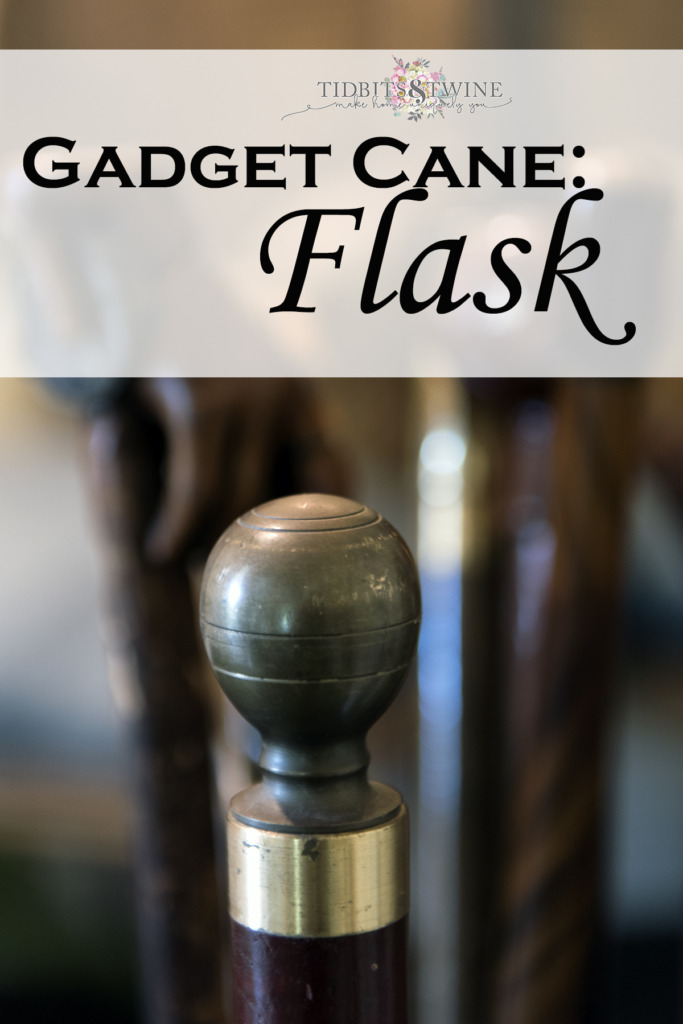 closeup of antique flask gadget cane with metal ball handle