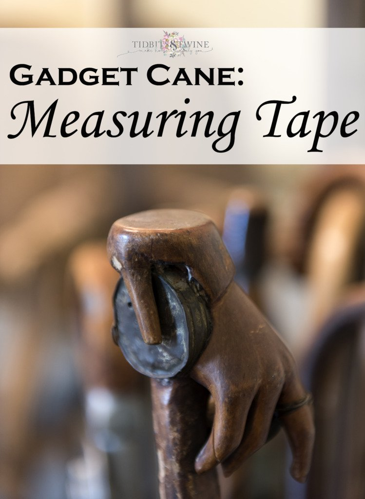 closeup of measuring tape gadget cane showing wooden hand handle holding metal tape measure