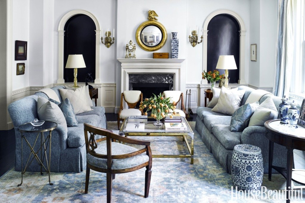 blue and white traditional living room with gold mirror above the fireplace