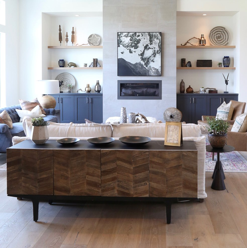 contemporary living room with buffet behind sofa and built in shelving next to fireplace