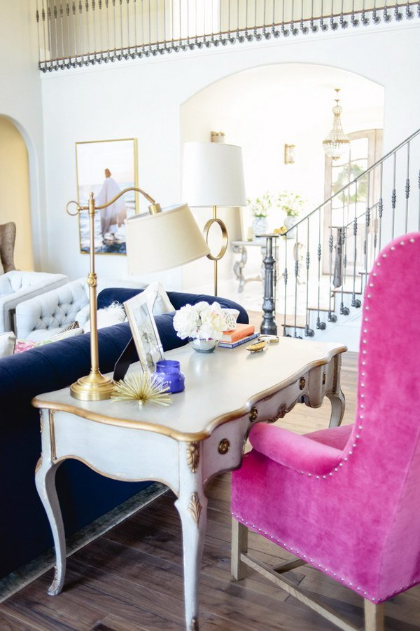 living room with french desk behind sofa with large pink desk chair