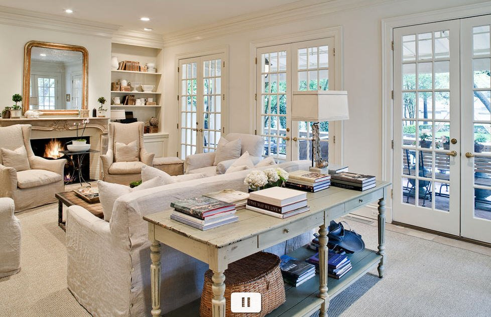 white french living room with large sofa table stacked with books and built ins by fireplace