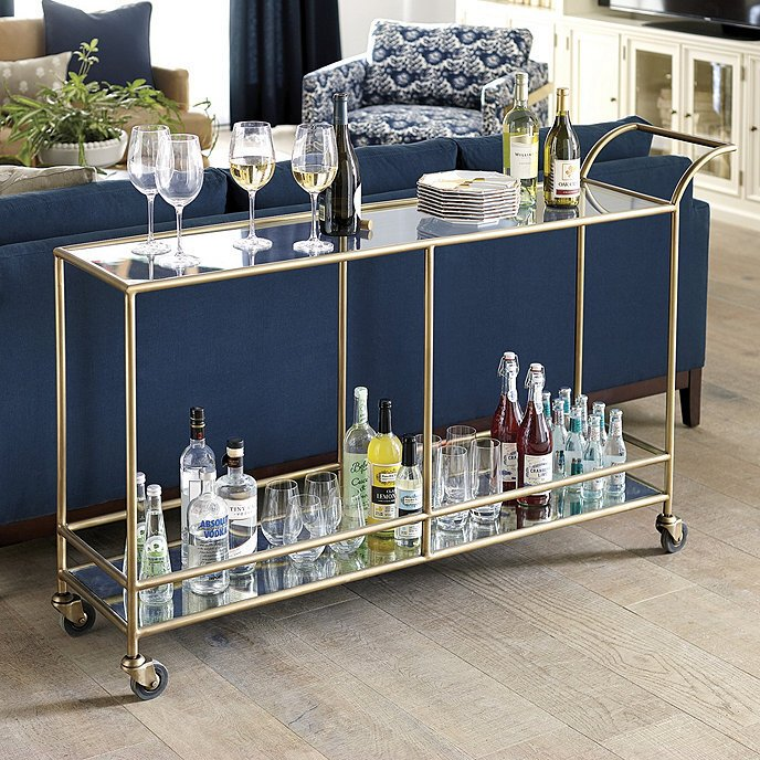 gold and glass bar cart behind a navy blue sofa in a traditional living room