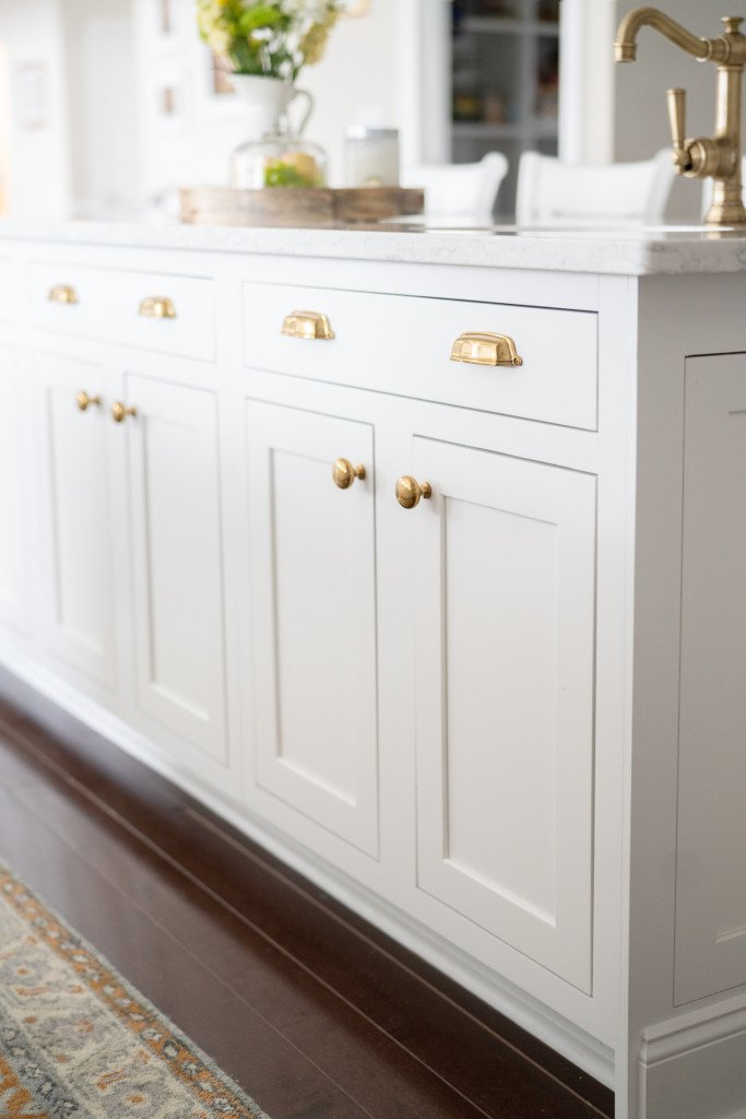 closeup of kitchen island with white inset cabinets and gold hardware