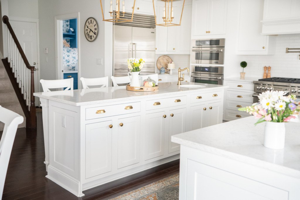 white kitchen with inset cabinets and gold hardware and wood floors