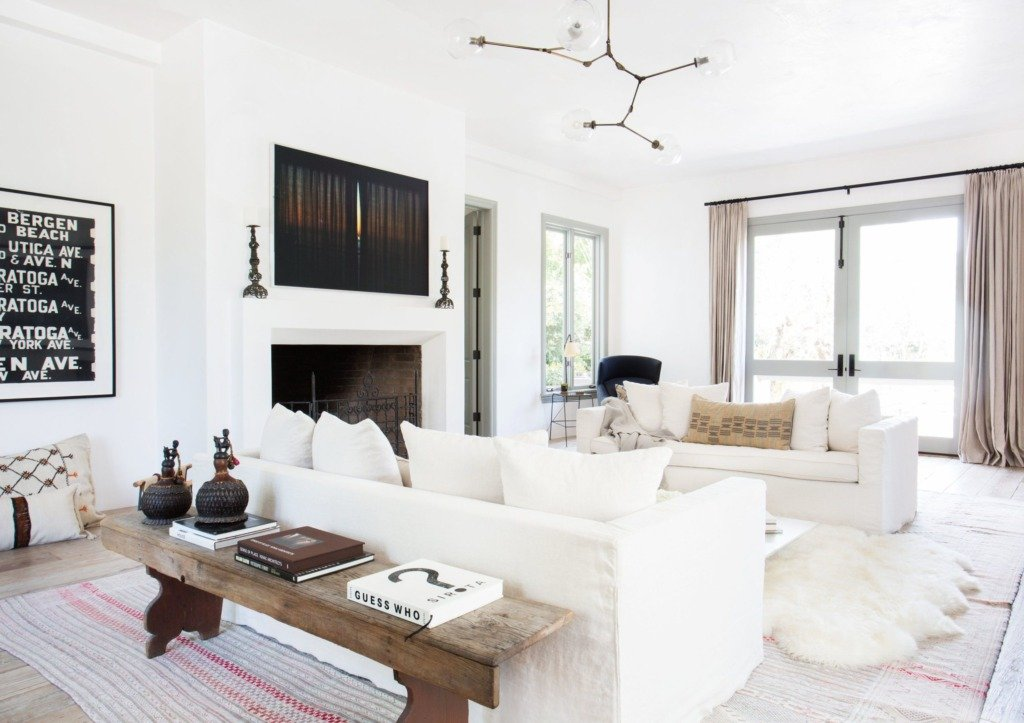 white living room with rustic wood bench behind white slipcovered sofa