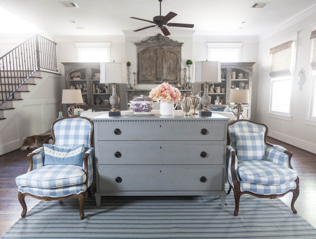 gray chest of drawers with blue and white check chairs on either side behind a sofa in a french living room