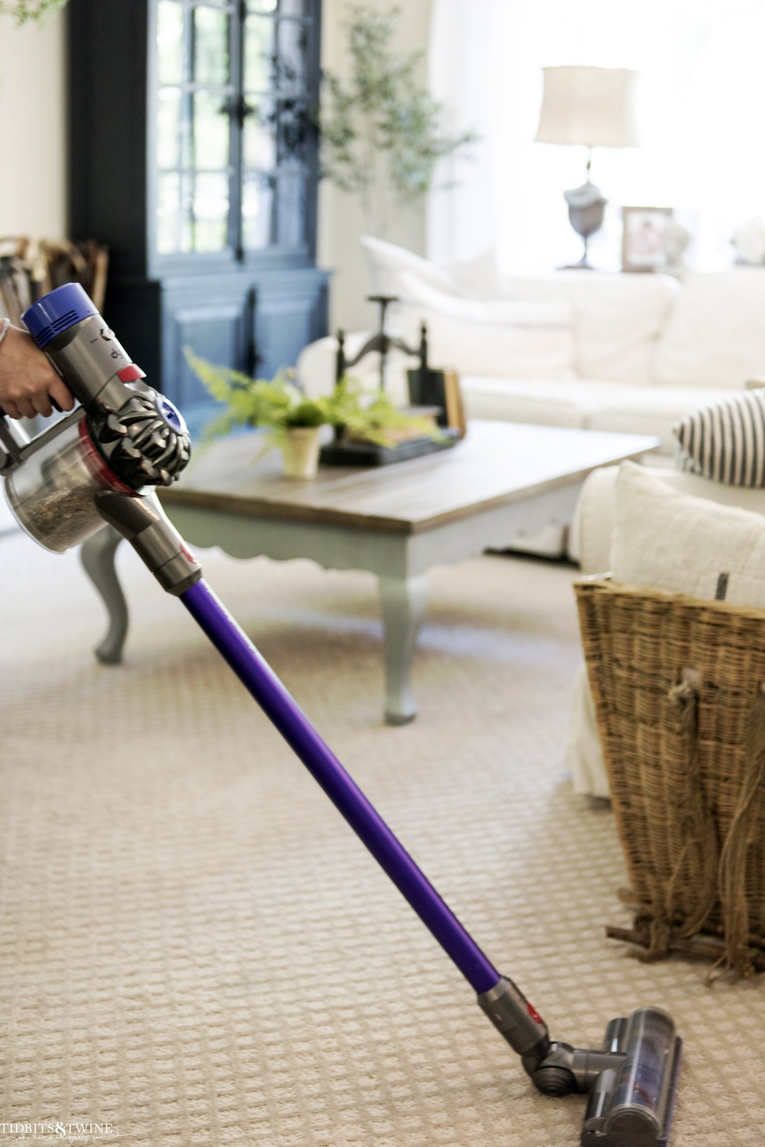 dyson cordless vacuum in french family room on diamond beige carpet with sectional in the background