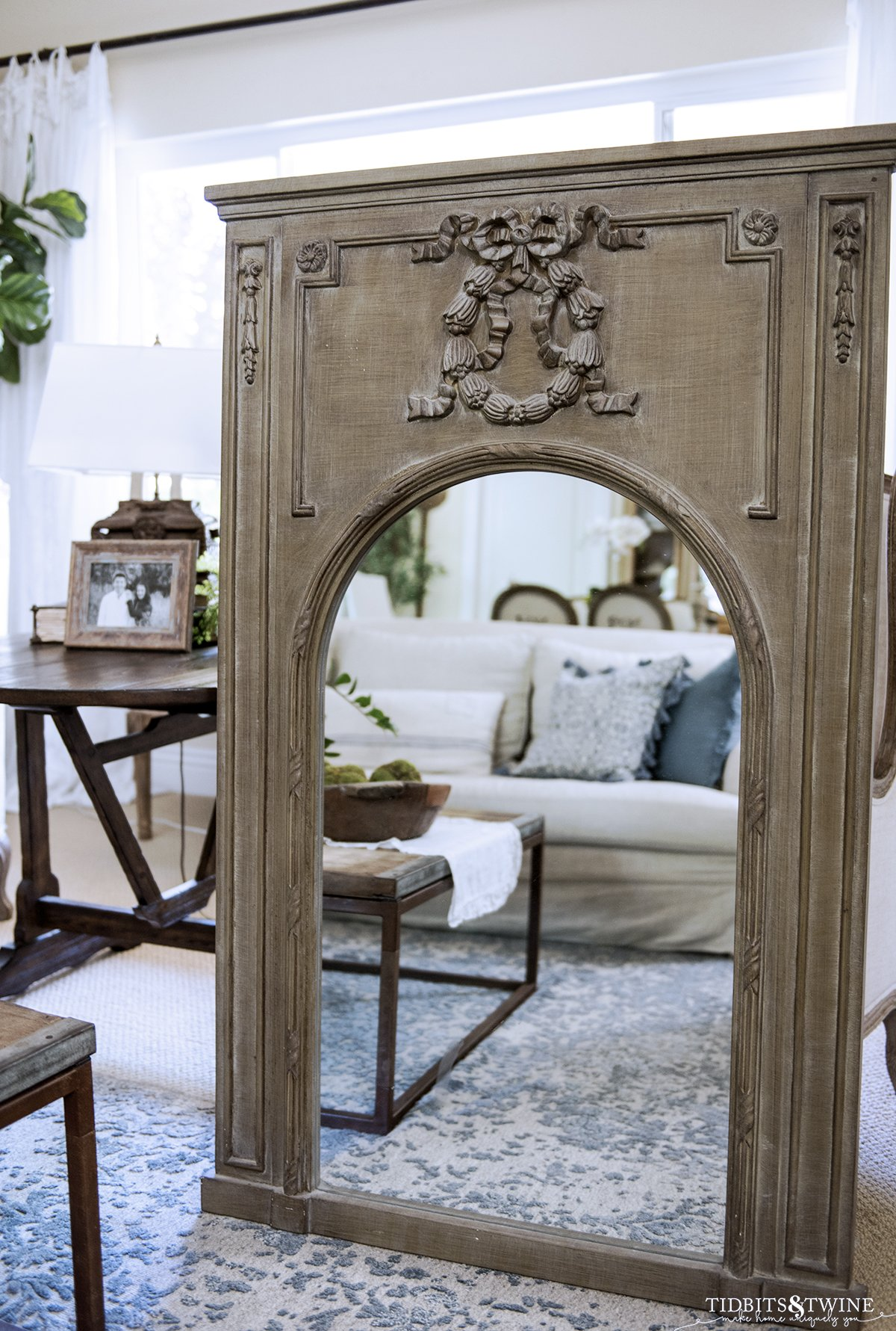 green distressed trumeau mirror with arched mirror propped up in a living room