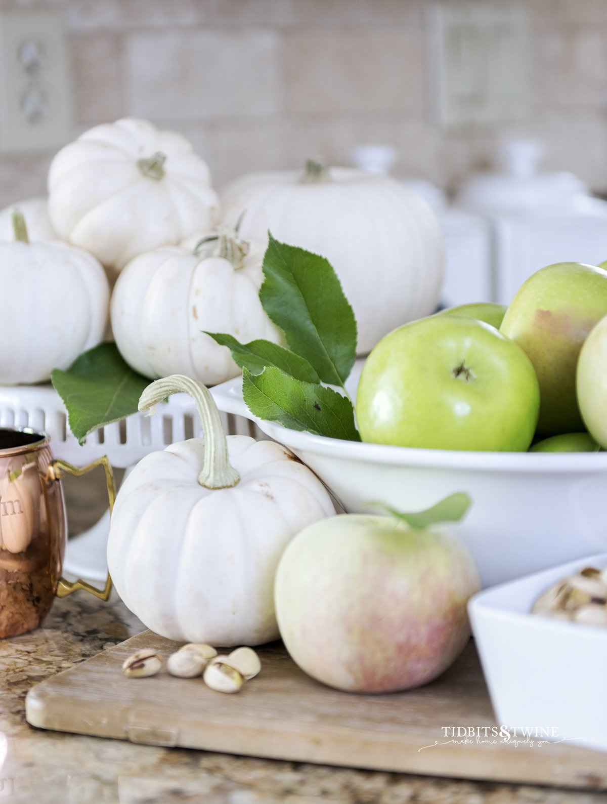 Fall vignette of green apples in a white bowl with white pumpkins on a cake stand, pistachios and a copper mug