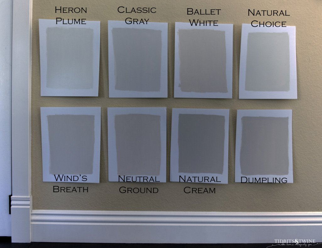 8 off white paint samples on white foam core taped to a yellow wall with white baseboard and dark wood floor
