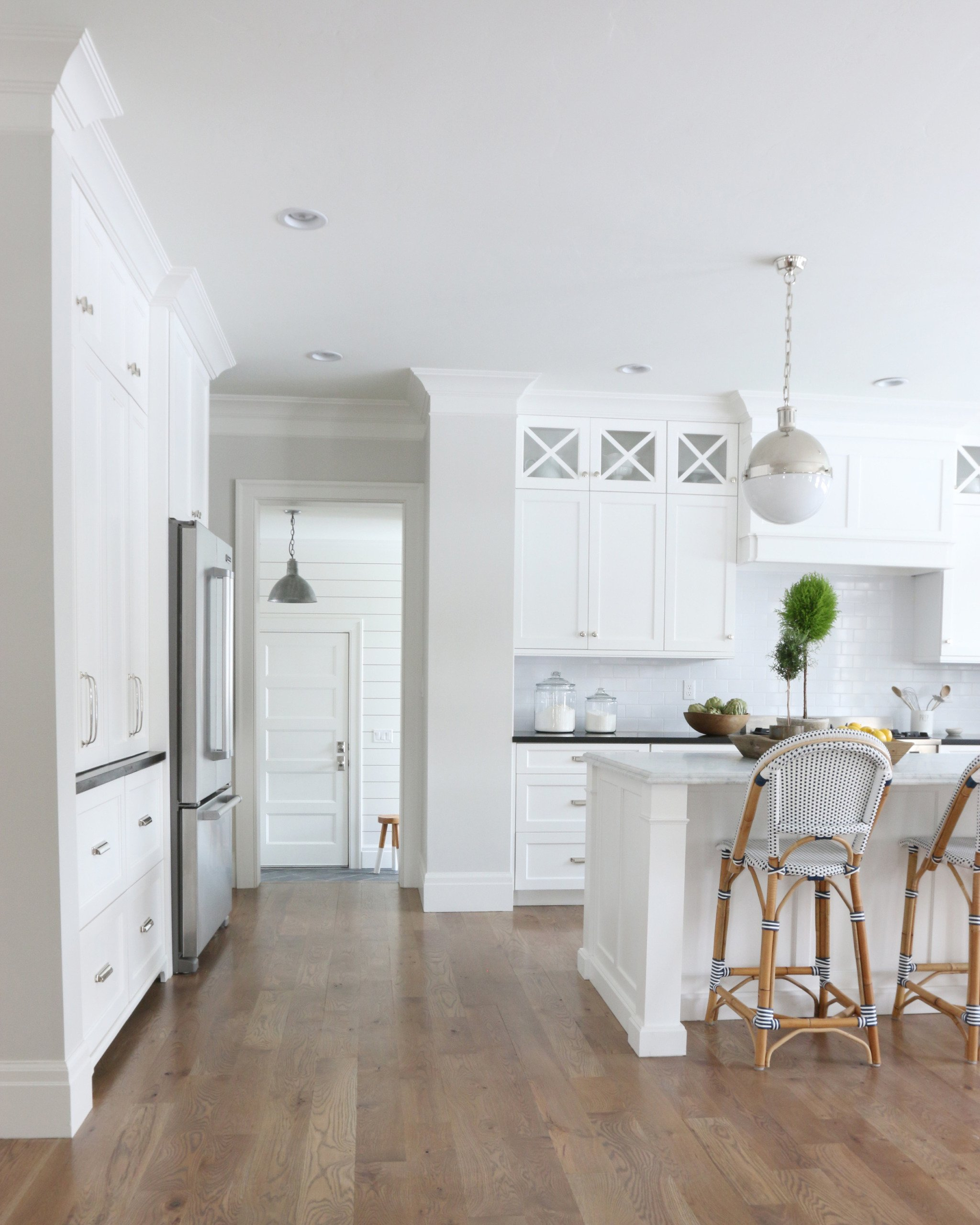 White kitchen cabinets with classic gray paint walls and serena and lily barstools and white subway tile backsplash wood floors