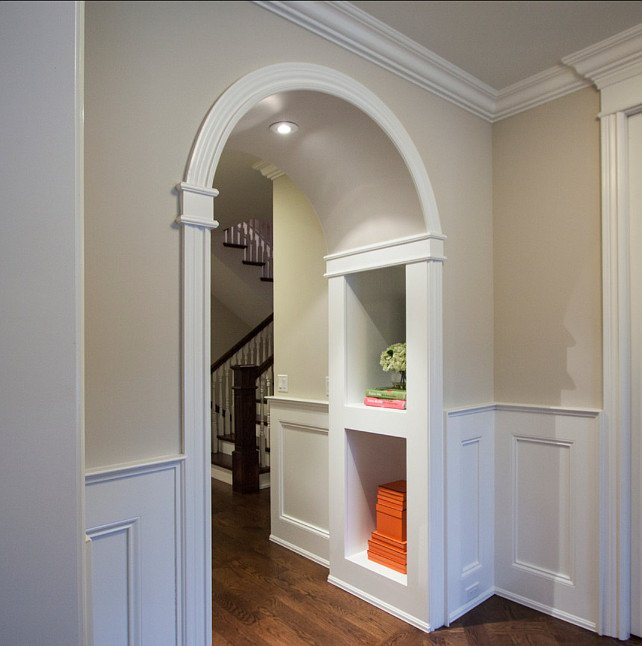 hallway painted natural cream with white wainscotting and arched doorway trimmed with molding and wood floors