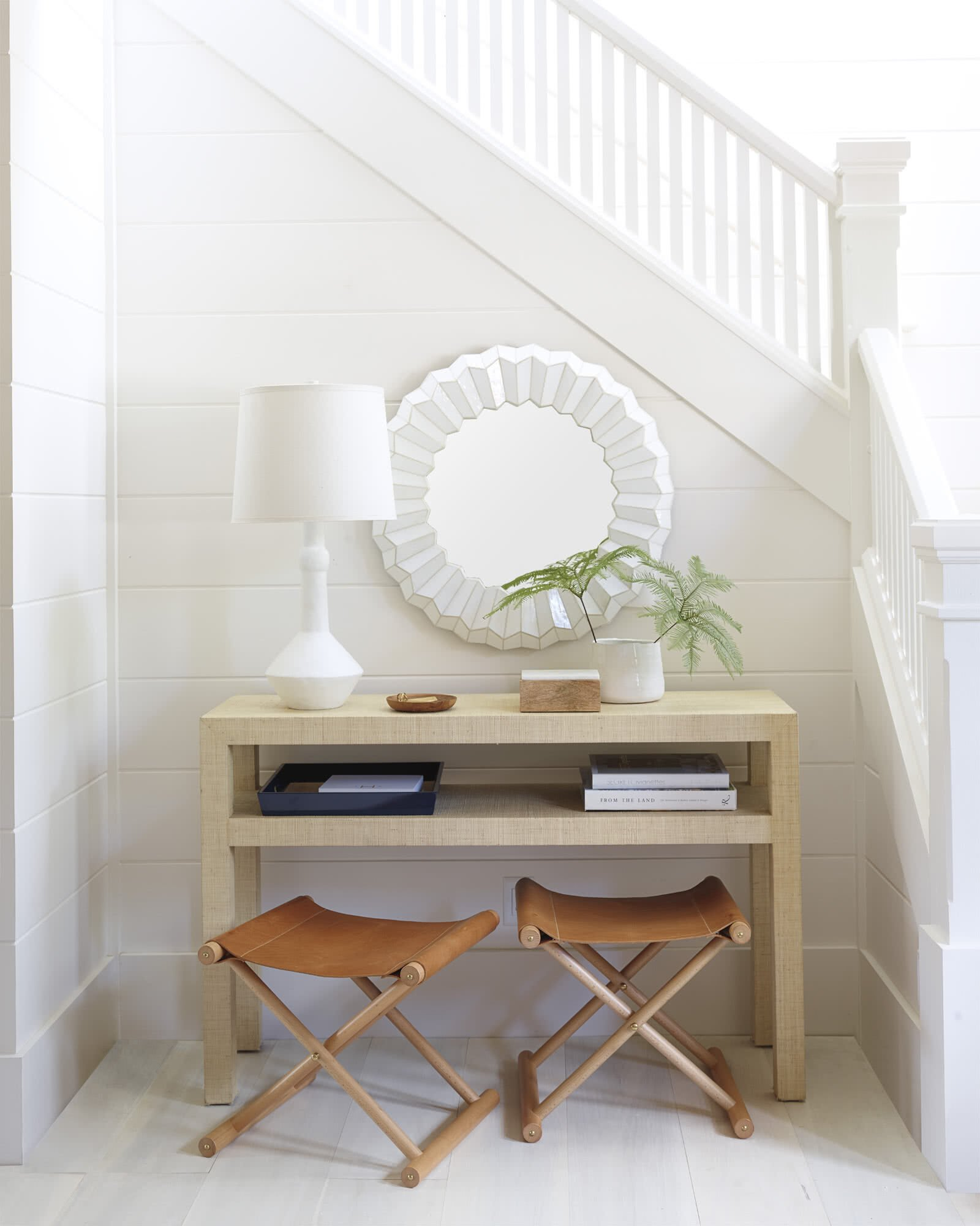white shiplap walls at bottom of stairs with console table in front and two brown leather campaign stools underneath