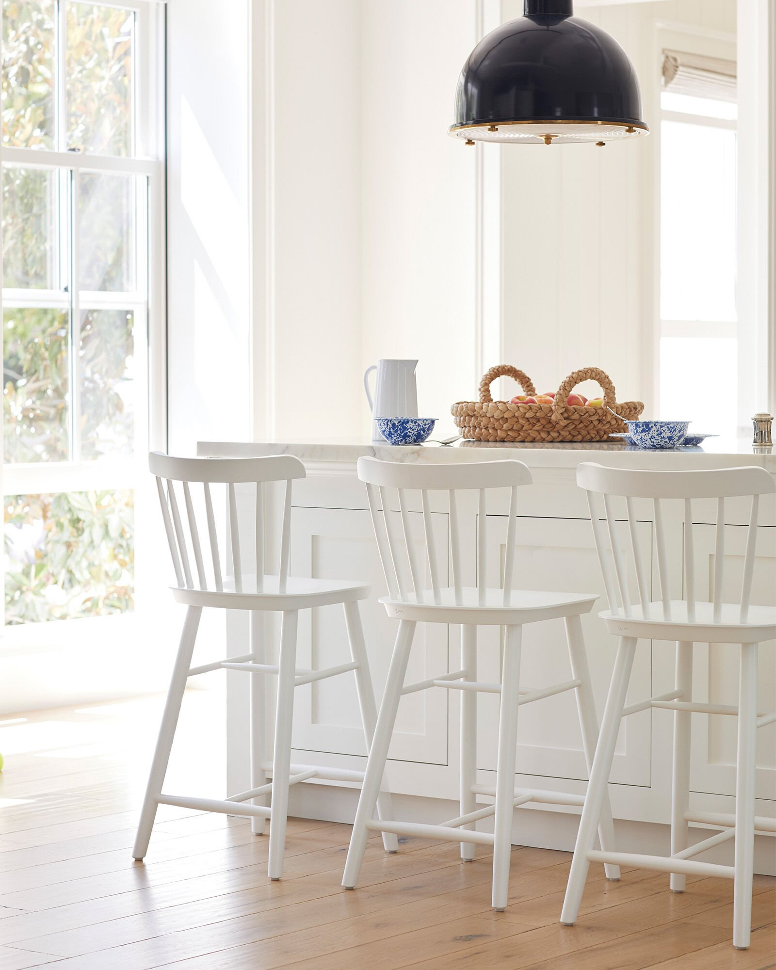 white wood counter stools in pure white kitchen with blue cereal bowls on counter and woven rattan tray full of apples