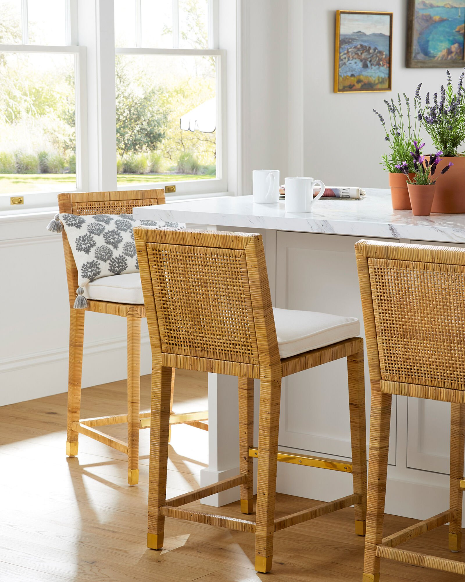 serena and lily rattan mariah counter stool with white cushion and brass leg caps in a white kitchen with wood floors