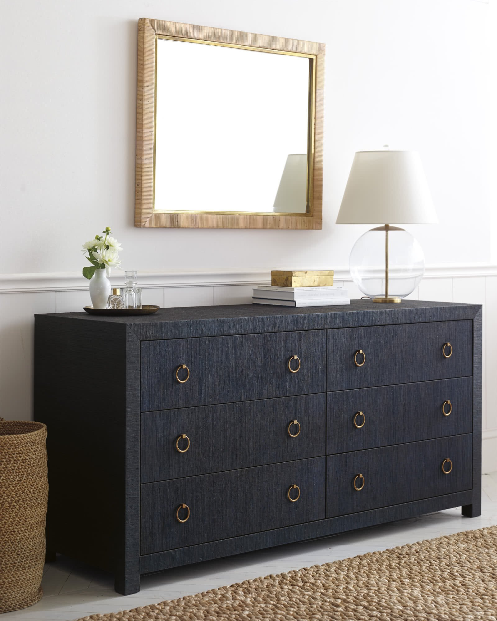 navy blue raffia wrapped six drawer dresser with gold hardware and sisal rug in front with glass and gold lamp on top