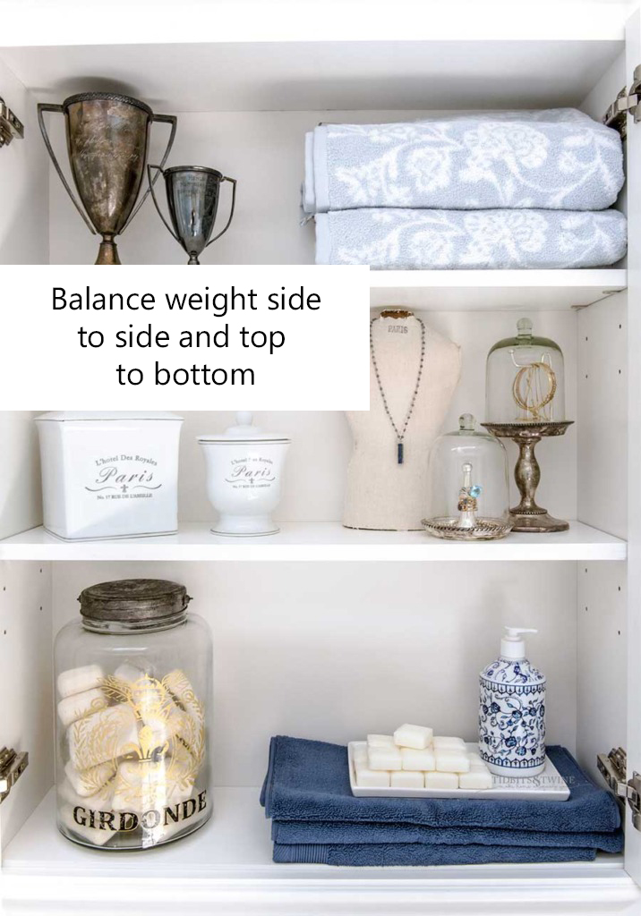 White bathroom shelves styled with with blue folded towels jewelry cloches vintage trophies soap displays