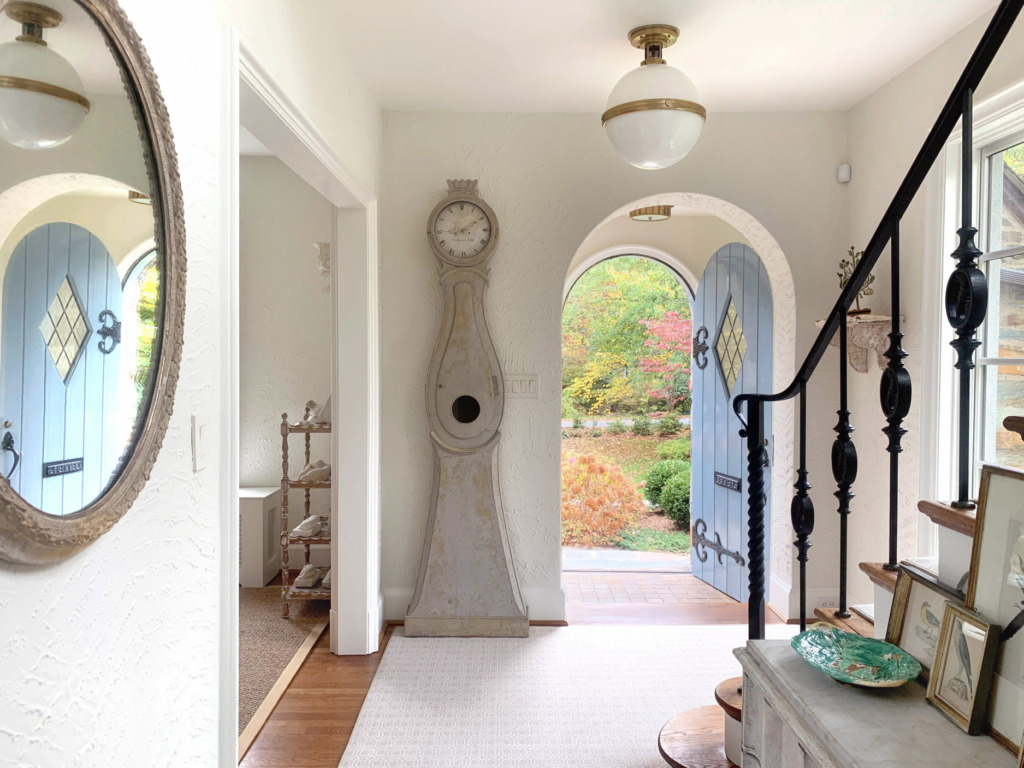 white walled foyer with gray mora clock next to arched front door that is painted blue