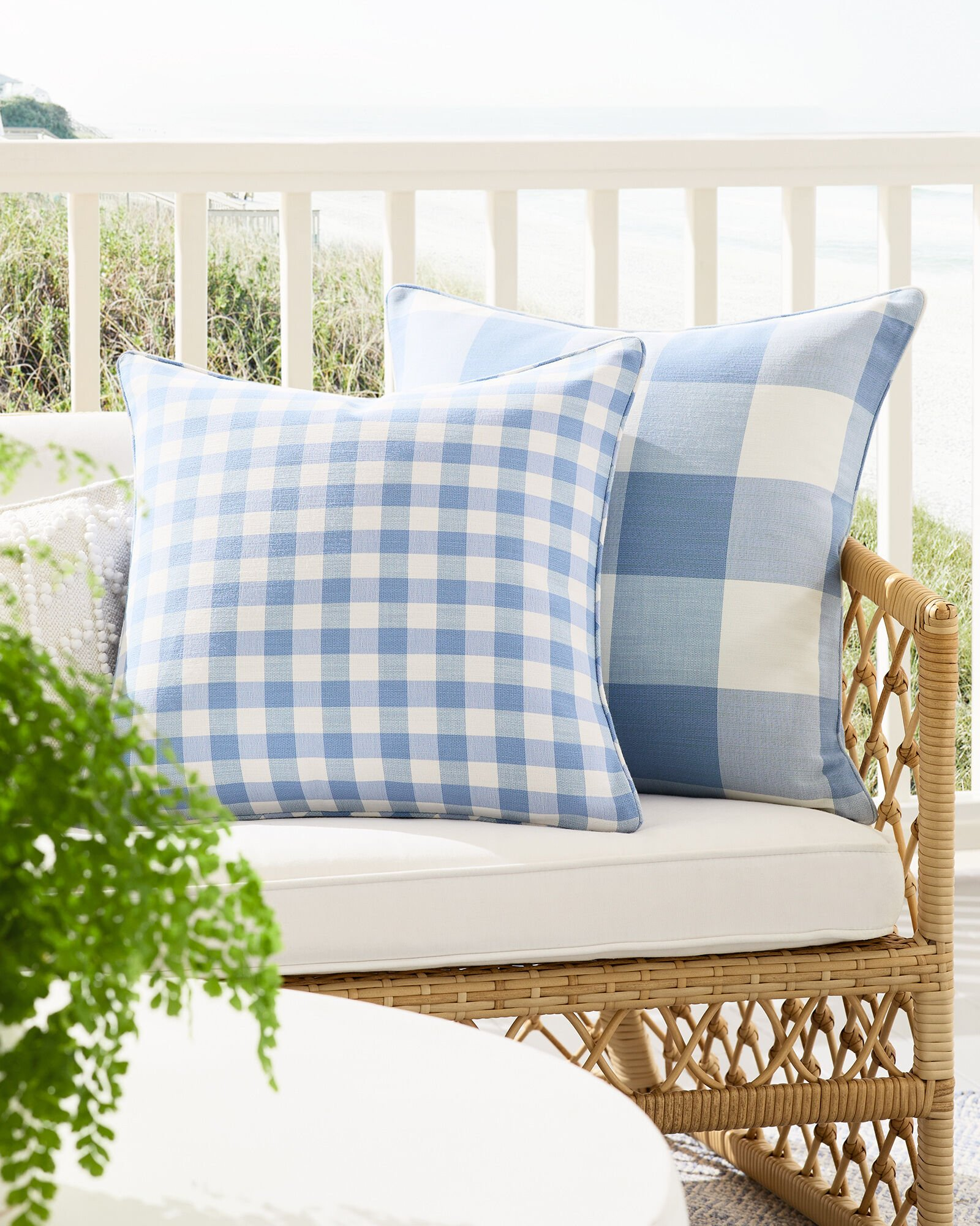 two outdoor blue and white gingham pillows on a wicker sofa with white cushion in front of a white railing