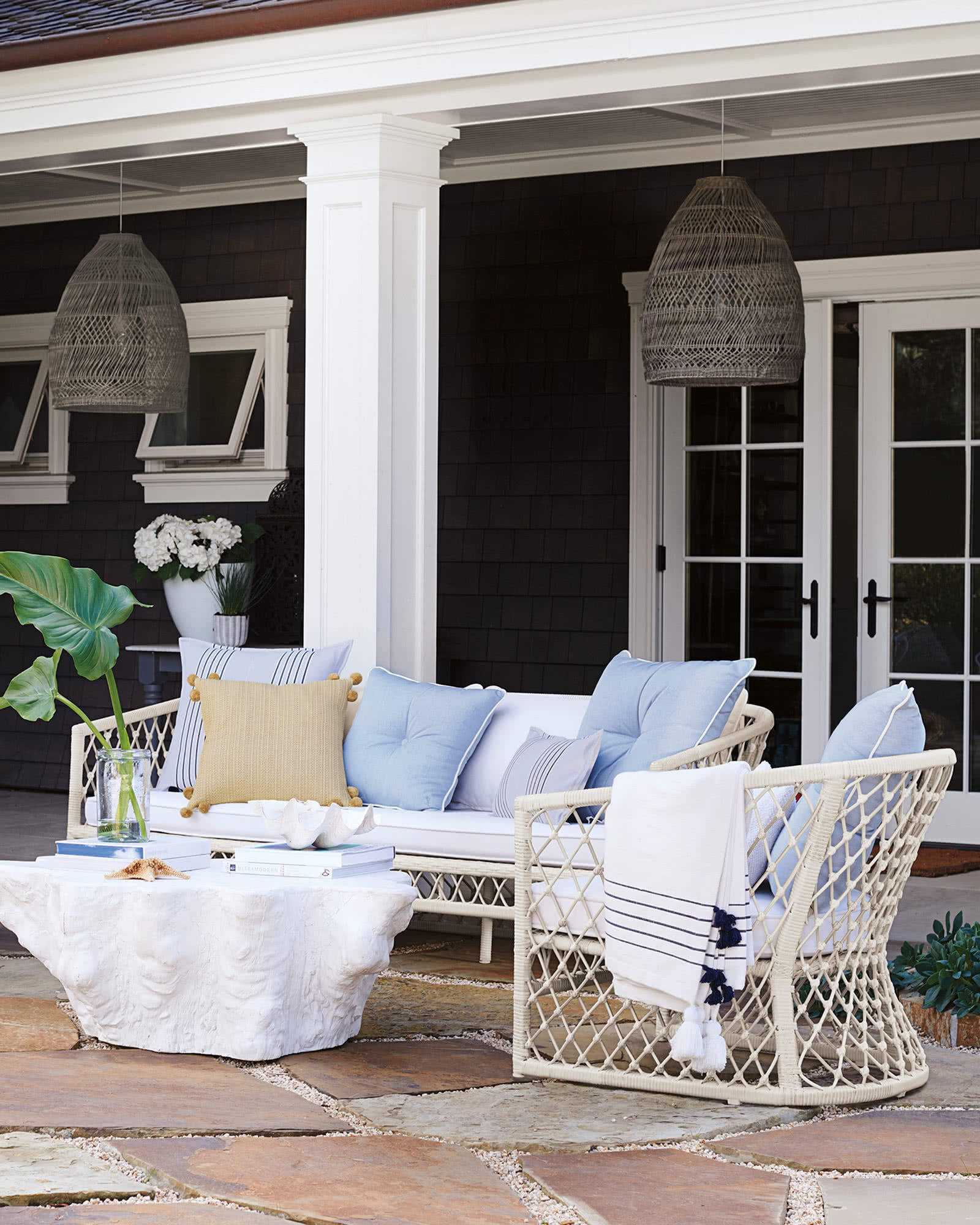 Outdoor patio seating area with two large serena and lily bell pendents and white wicker furniture with blue toss pillows