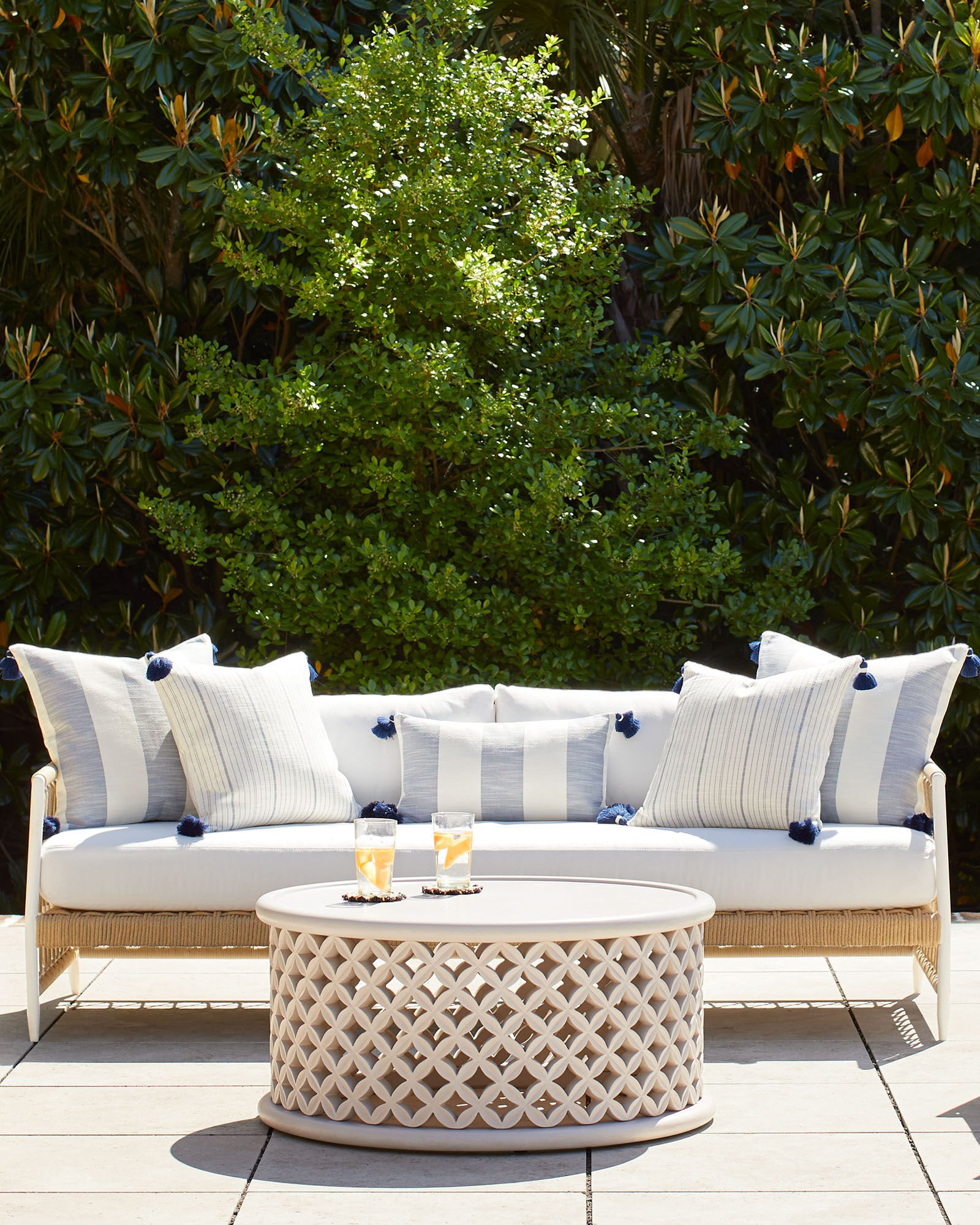 outdoor sofa on patio with white cushions and blue and white striped pillows and round white coffee table