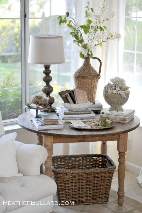 antique wooden table in corner of living room windows with books baskets and shells on top and a large basket underneath