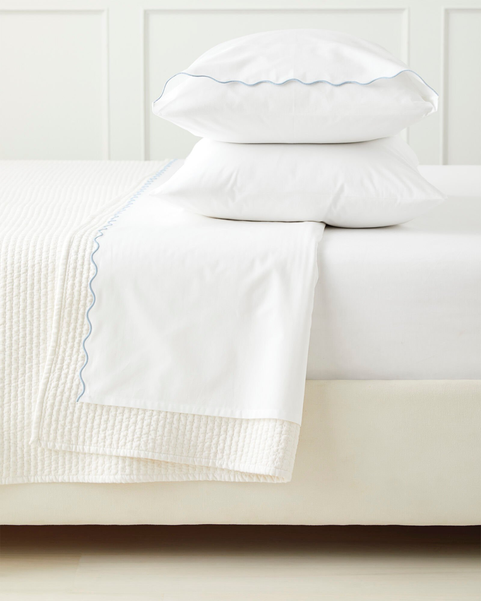 closeup of white upholstered bed with white quilt and white sheets that have a blue scallop trim