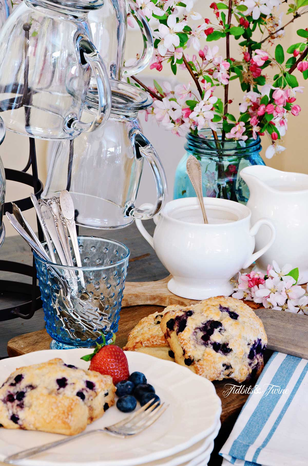 Breakfast vignette showing blueberry scones next to bottle drying rack holding clear glass mugs and pink flowers in the background