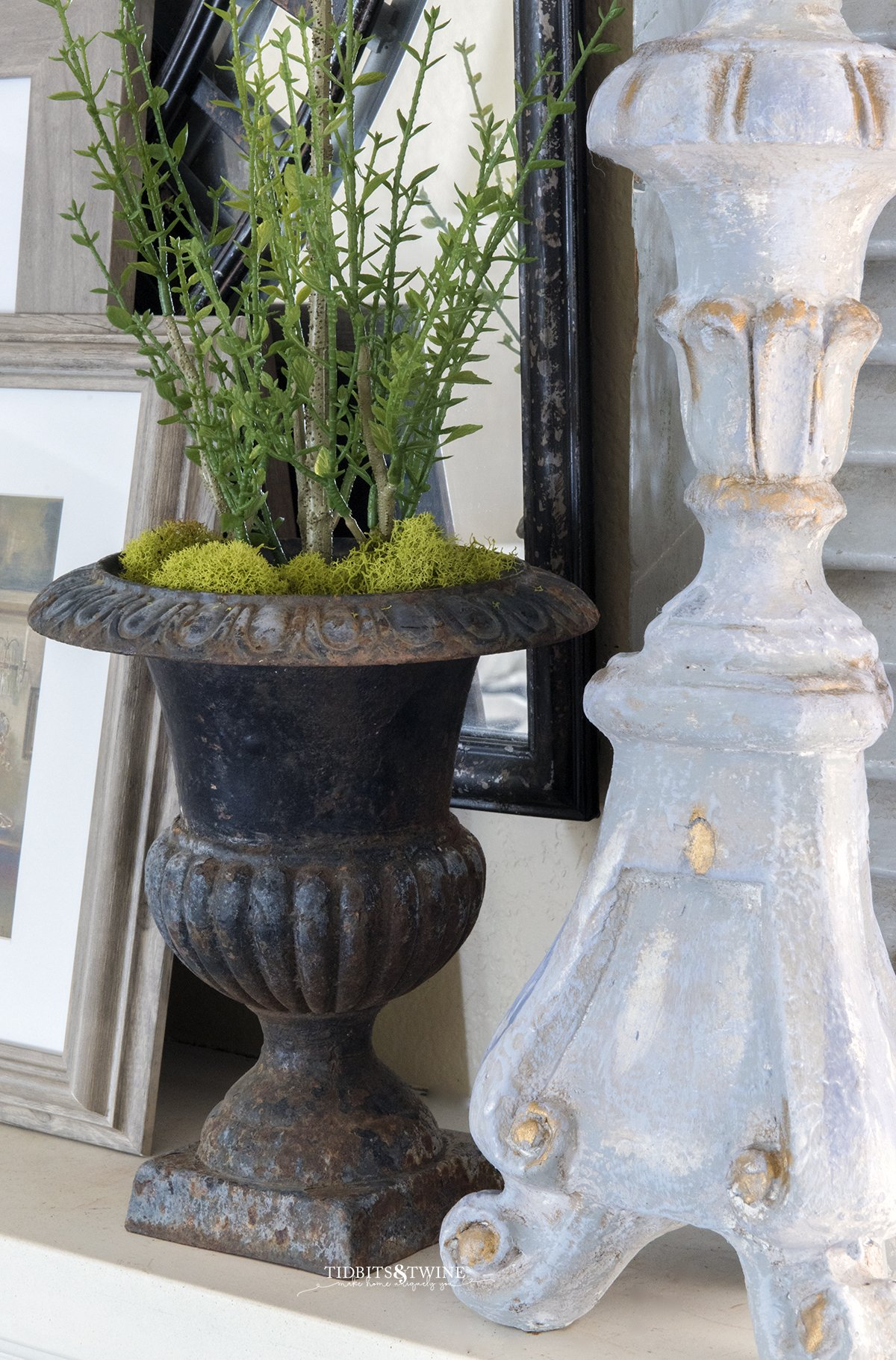Closeup of antique french metal urn with myrtle topiary inside and green moss at base next to a french candlestick on a mantel