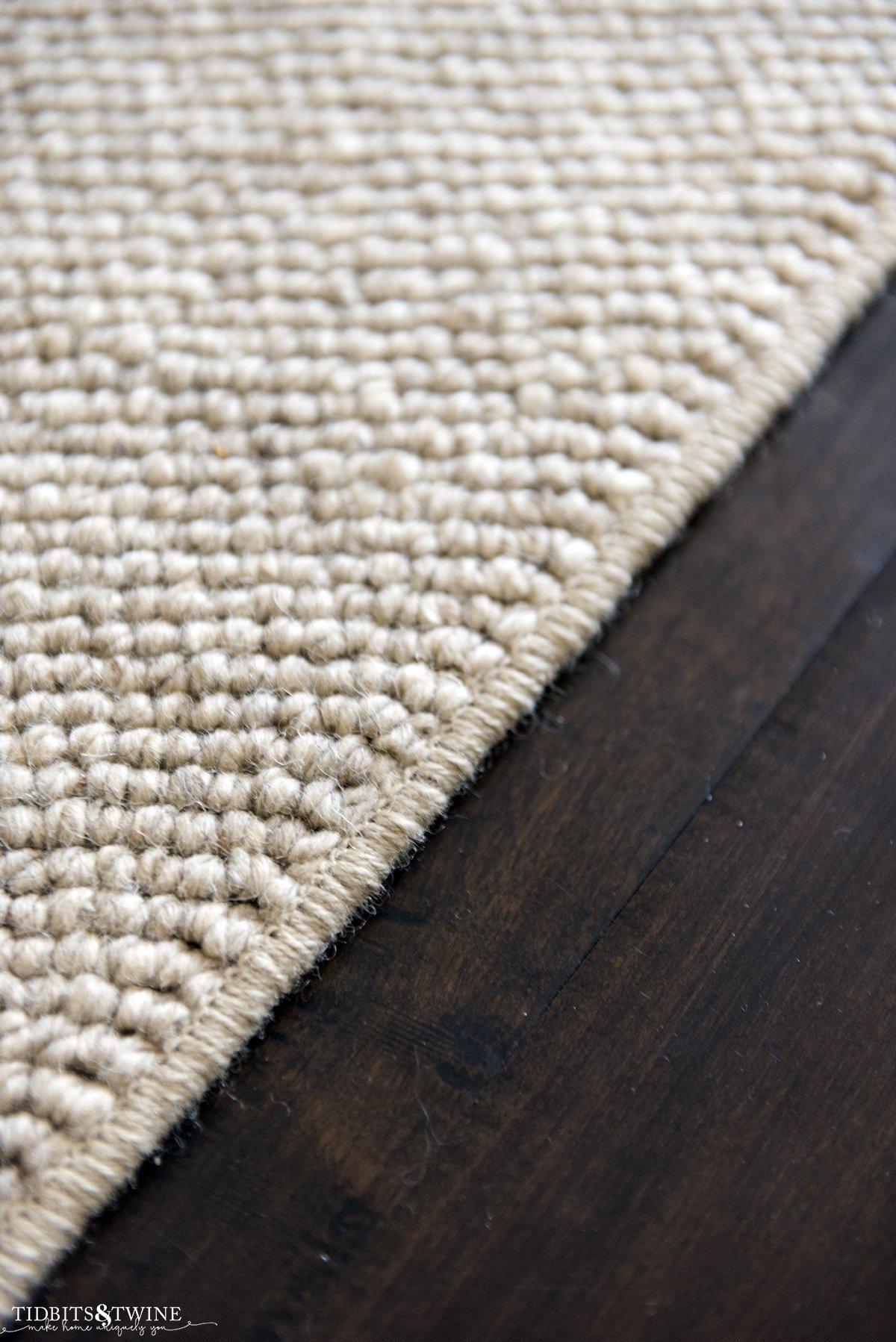 closeup of beige wool loop custom rug with standard surged edges on dark wood floor