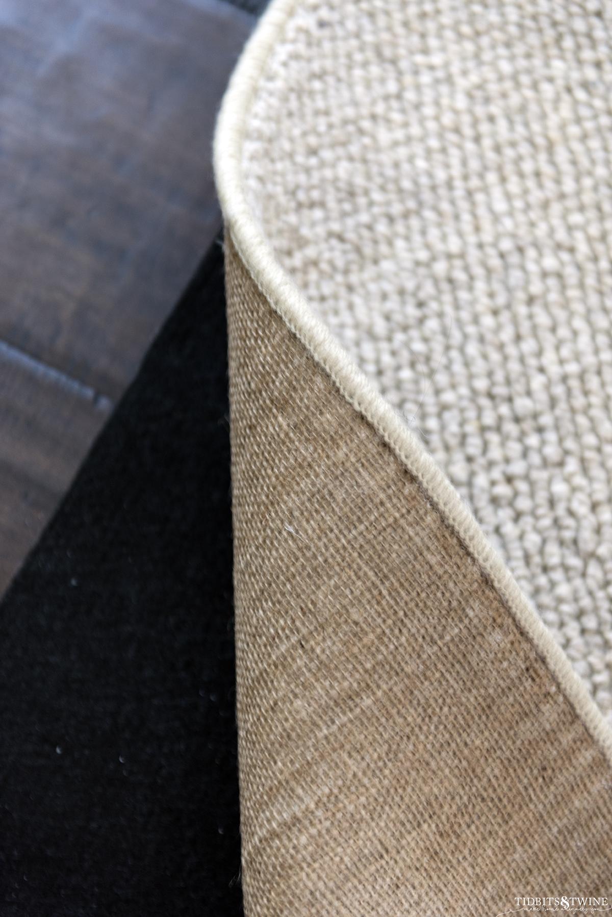 closeup of custom wool area rug backing and black rug pad underneath on brown wood floor