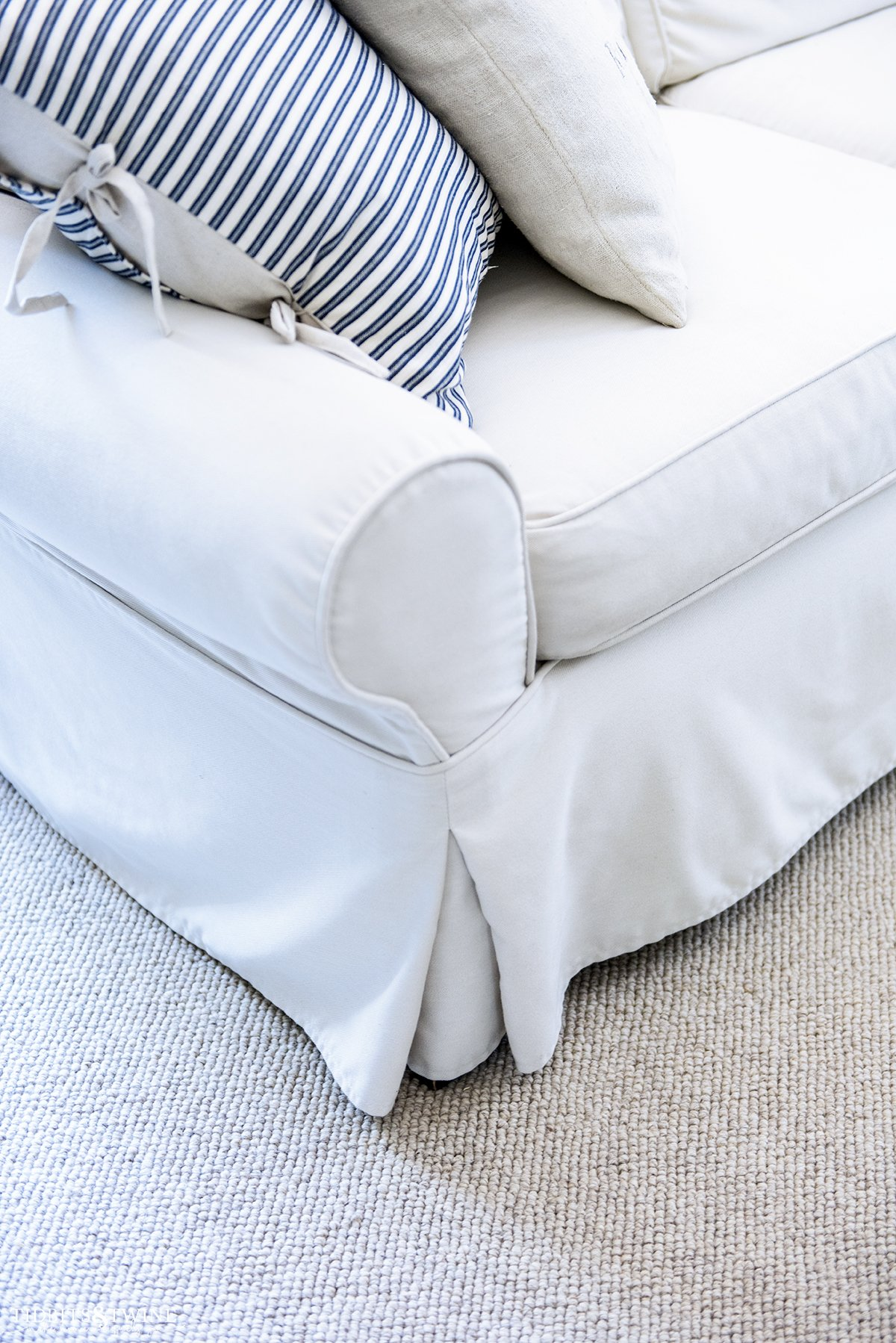 closeup of slipcovered sofa with blue stripped pillow on top next to grain sack pillow and loop wool area rug beneath