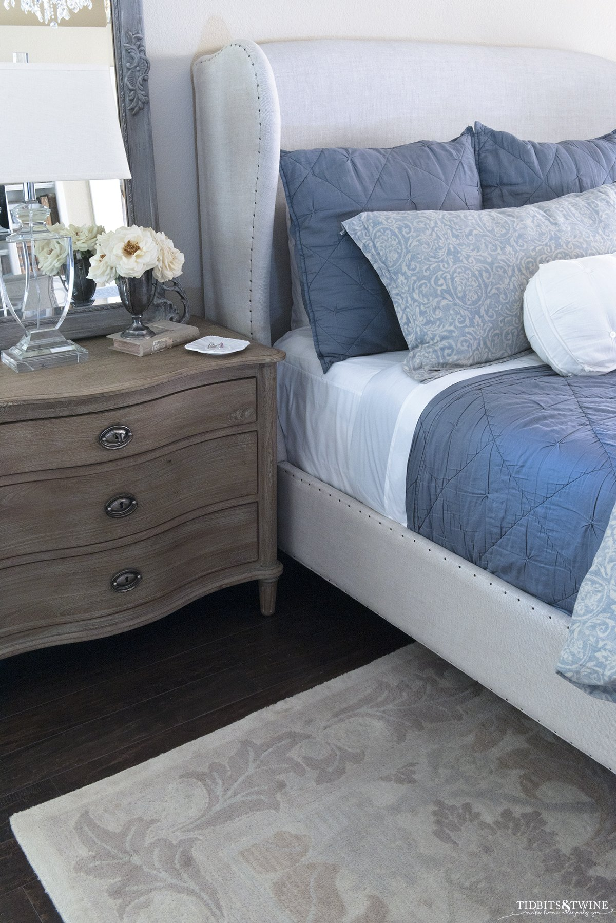 linen wingback bed with french nightstand topped with french mirror and crystal table lamp