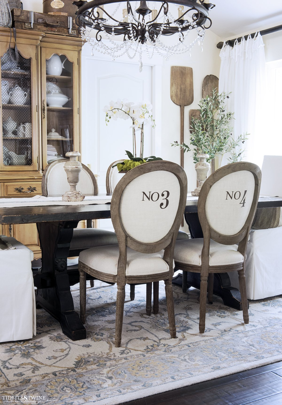 french style dining room with linen and wood chairs with numbers on the back and french hutch containing antique ironstone collection