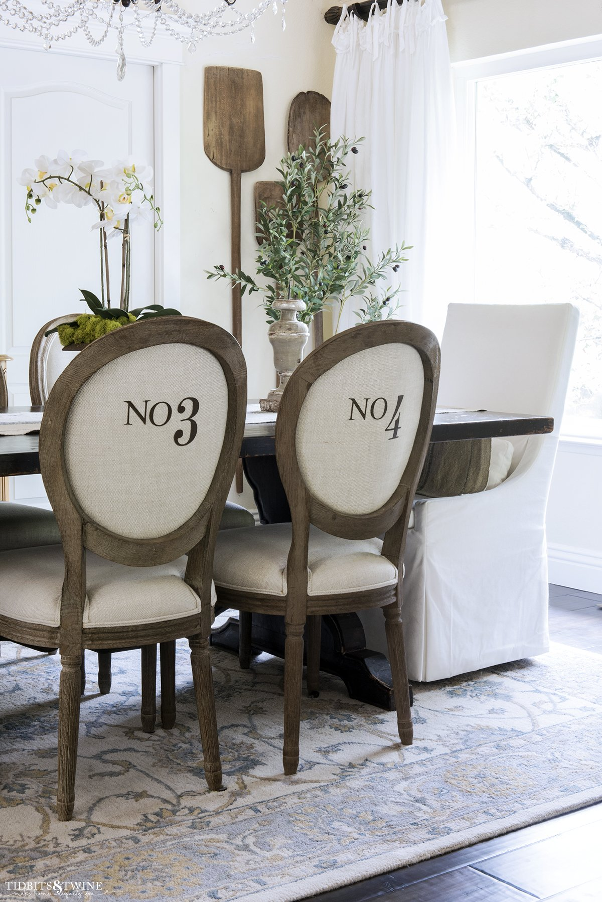 Dining room trestle table with french chairs with numbers on the back and white velvet head chair