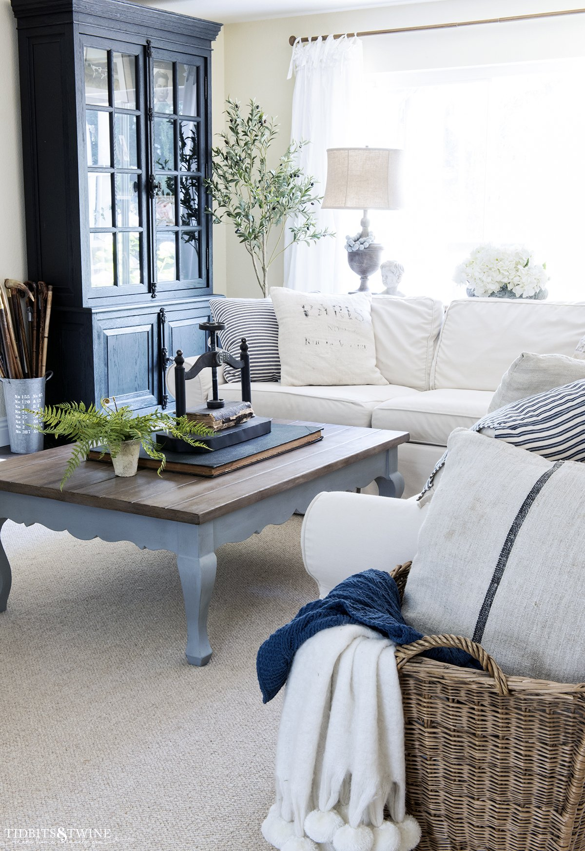 white slipcovered sectional with french coffee table with book press and fern on top and custom wool area rug