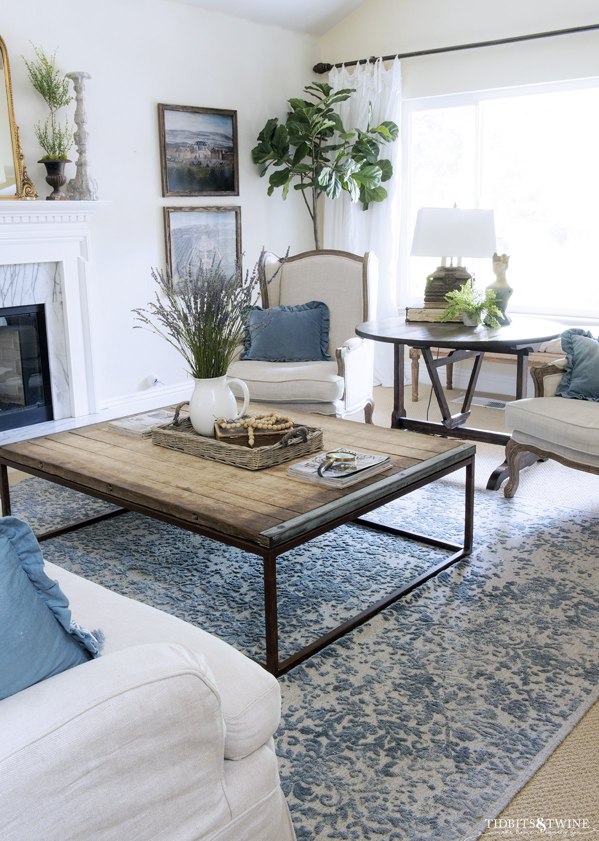 French inspired living room with two wingback chairs and industrial coffee table in front of white marble fireplace