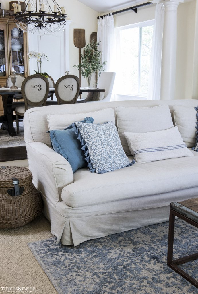 slipcovered living room sofa with blue pillows and blue rug underneath looking into french dining room with numbered chairs