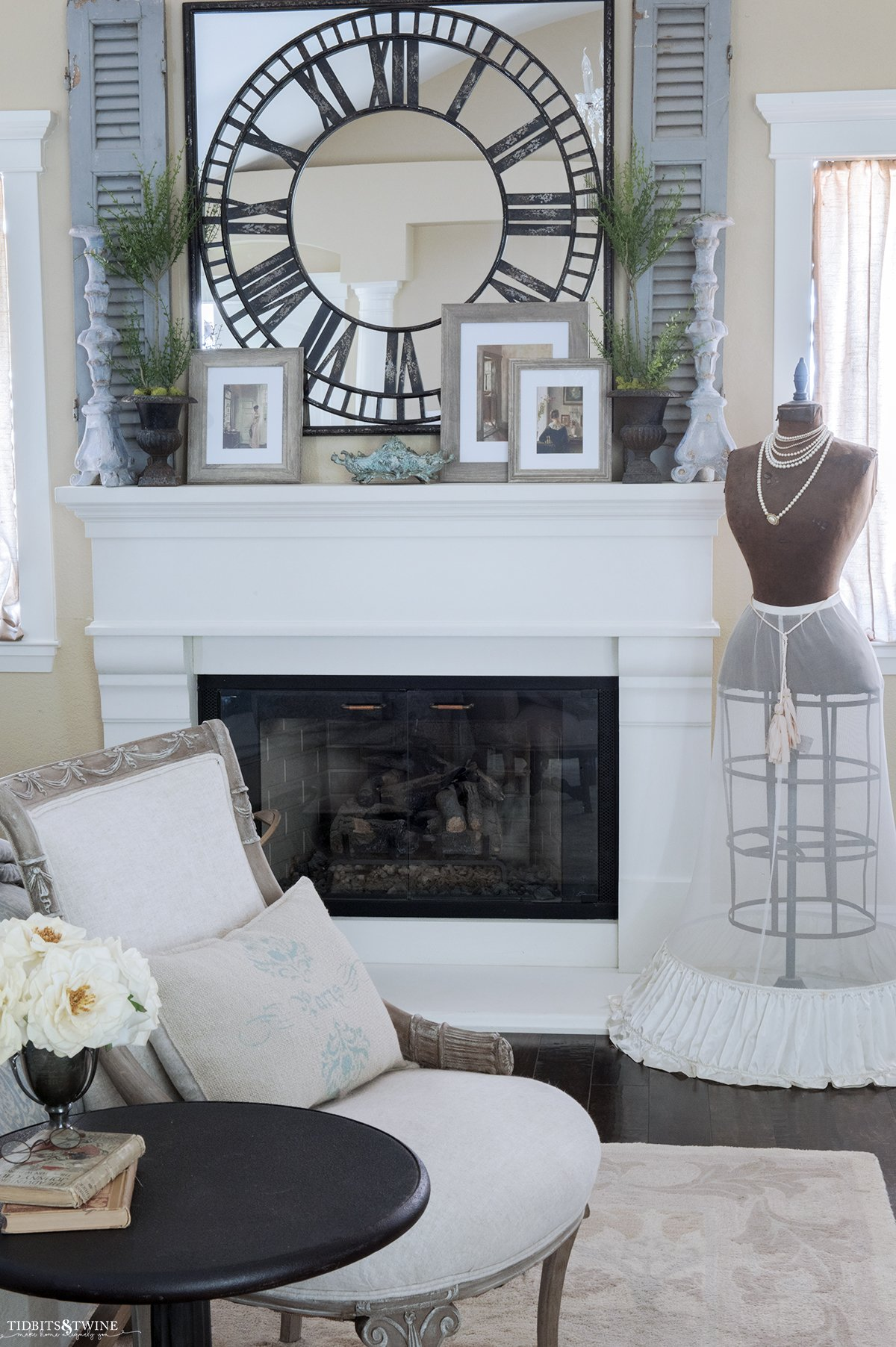 french seating area at end of bed looking toward white cast stone fireplace mantel with mirror and candlesticks above and antique dress form on side