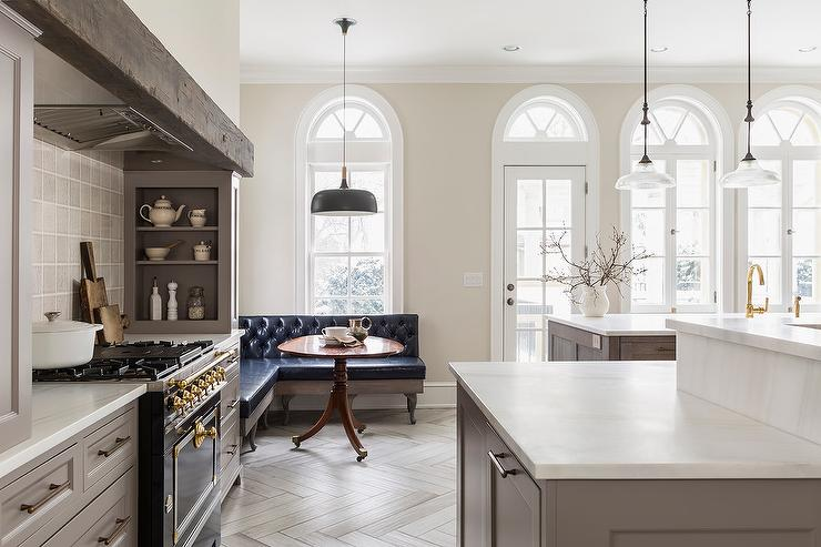 traditional kitchen painted winds breath with gray cabinets and black stove with beam over chimney and herringbone wood floors