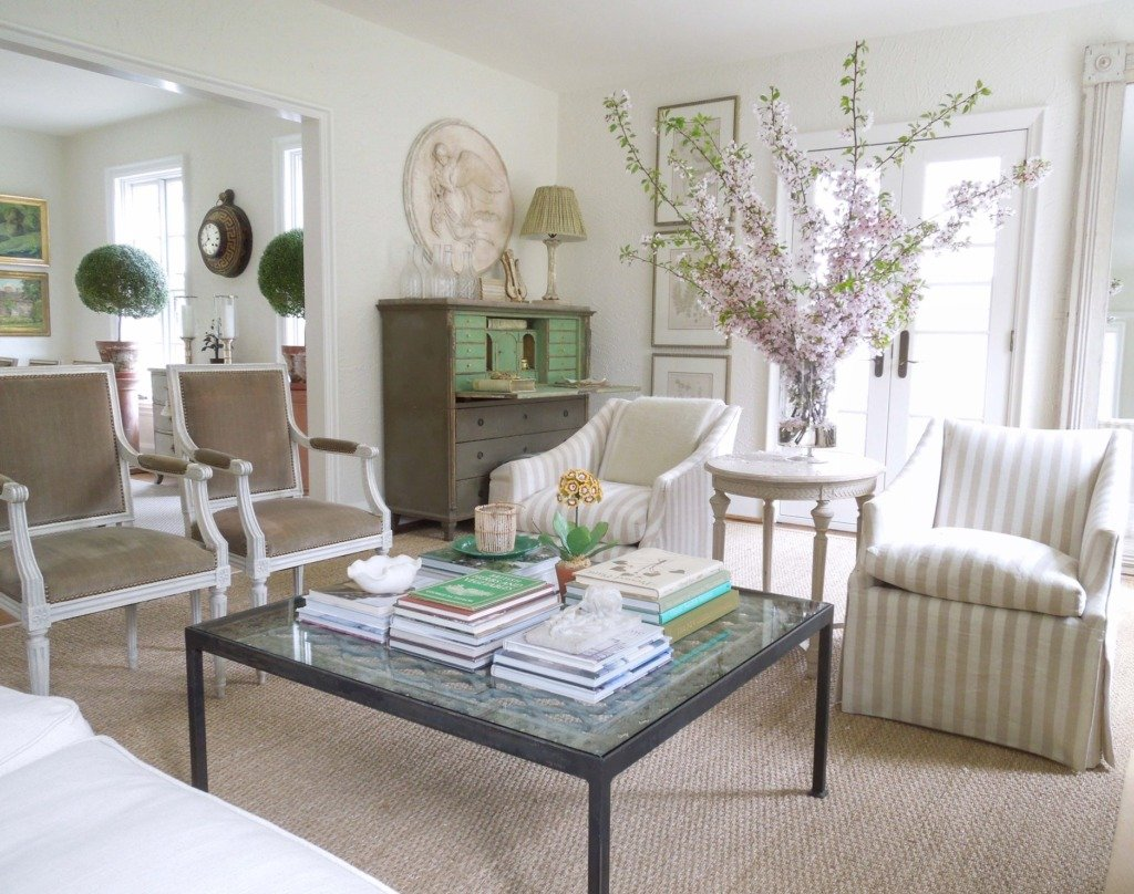 living room with striped slipcovered chairs next to glass square coffee table and gustavian secretary in the background