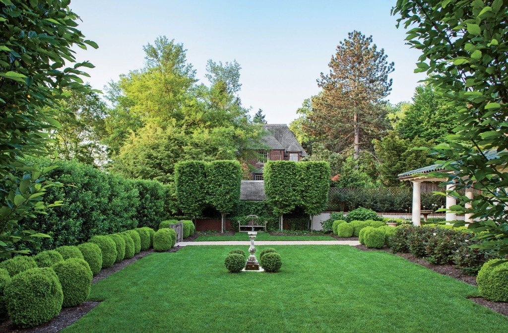 formal backyard garden with lawn surrounded by topiary hedges and antique sundial in center of lawn